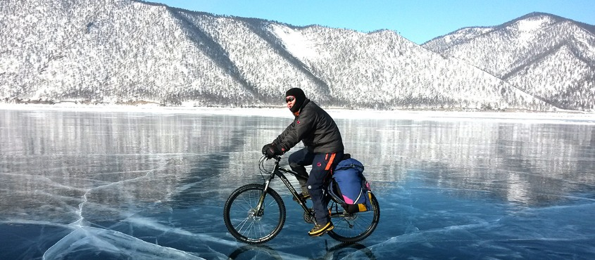 Cycling winter adventure on crystal clear lake Baikal